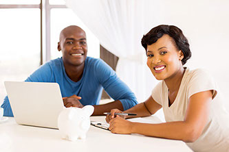 Image of young couple with laptop and piggy bank.